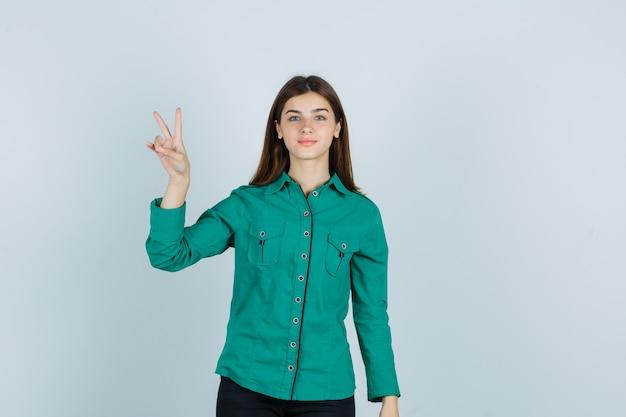 Jovem senhora de camisa verde, mostrando o gesto de vitória e olhando confiante, vista frontal.