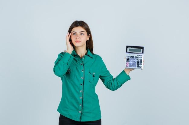 Jovem senhora de camisa verde segurando calculadora enquanto toca as têmporas e olhando pensativa, vista frontal.
