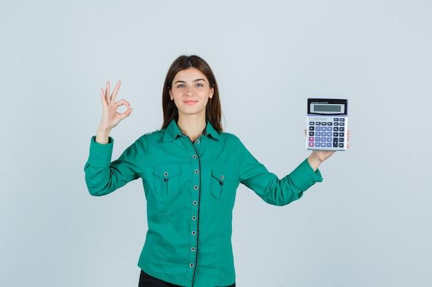 Jovem senhora de camisa verde segurando calculadora, mostrando o gesto de ok e olhando alegre, vista frontal.