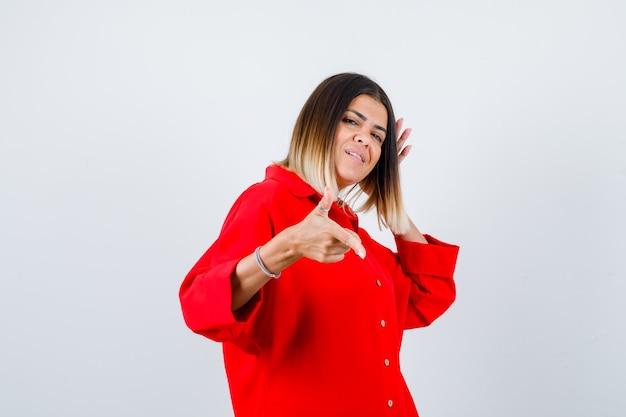 Jovem senhora de camisa vermelha grande, apontando para o lado e olhando alegre, vista frontal.