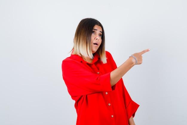 Jovem senhora de camisa vermelha grande, apontando para o lado e olhando perplexa, vista frontal.