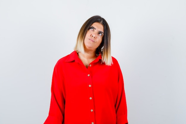 Jovem senhora de camisa vermelha grande, olhando de lado e olhando pensativa, vista frontal.