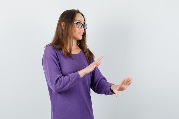 Jovem senhora de camisa violeta, fazendo gesto de desaceleração e olhando curiosa, vista frontal.