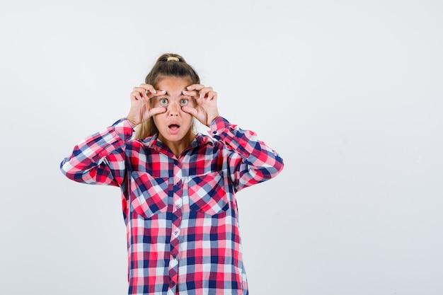 Jovem senhora de camisa xadrez, abrindo os olhos com os dedos e parecendo chocada, vista frontal.