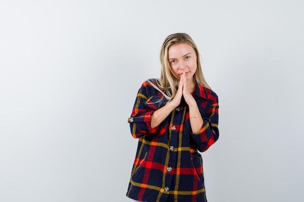 Jovem senhora de camisa xadrez, apertando as mãos para orar e olhando em paz, vista frontal.