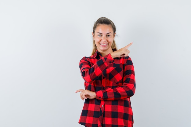 Jovem senhora de camisa xadrez apontando para o canto superior direito e parecendo alegre