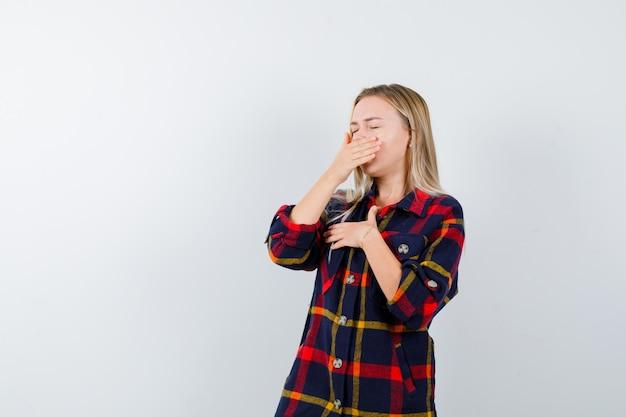 Jovem senhora de camisa xadrez, bocejando e parecendo com sono, vista frontal.
