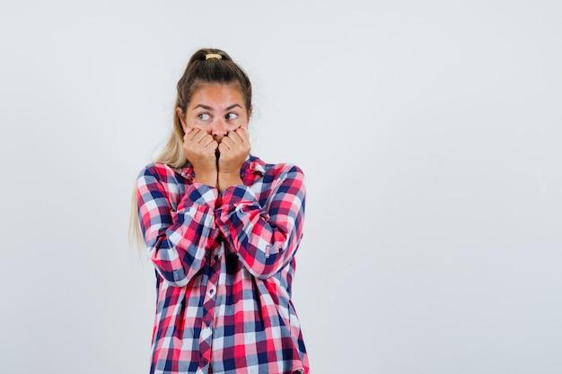Jovem senhora de camisa xadrez, com os punhos na boca e parecendo assustada, vista frontal.