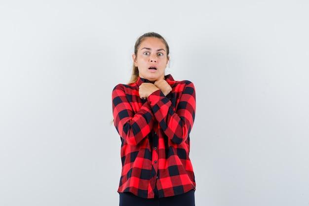 Jovem senhora de camisa xadrez de mãos cruzadas no peito e parecendo assustada