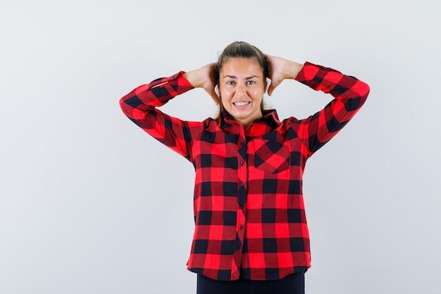 Jovem senhora de camisa xadrez de mãos dadas atrás da cabeça e parecendo alegre