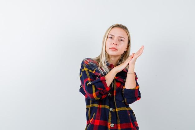 Jovem senhora de camisa xadrez, esfregando as mãos e olhando pensativa, vista frontal.