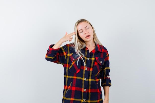 Jovem senhora de camisa xadrez fazendo gesto de suicídio e olhando sem esperança, vista frontal.