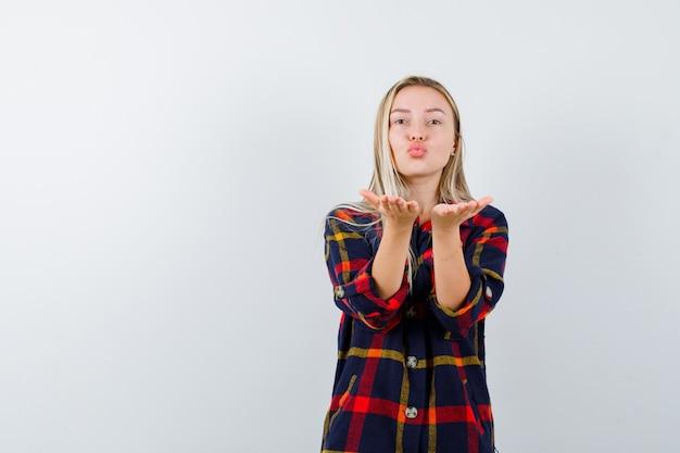 Jovem senhora de camisa xadrez mandando beijo com as mãos e está linda, vista frontal.