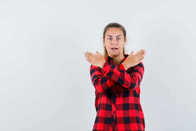 Jovem senhora de camisa xadrez mostrando gesto de pare e parecendo animada
