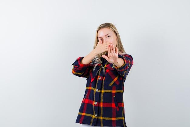 Jovem senhora de camisa xadrez, mostrando o gesto de parada, mantendo a mão na boca e olhando séria, vista frontal.