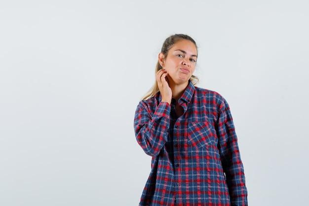 Jovem senhora de camisa xadrez, posando enquanto examinava sua pele e parecia tentadora, vista frontal.