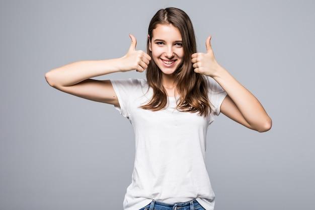 Jovem senhora de camiseta branca e calça jeans azul mostra os polegares para cima e canta na frente do fundo branco do estúdio
