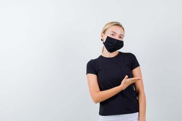 Jovem senhora de camiseta, calça e máscara médica dando as boas-vindas a algo isolado