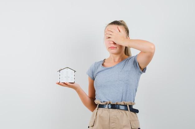 Jovem senhora de camiseta e calça segurando um modelo da casa e parecendo arrependida