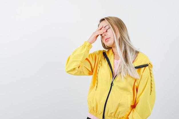 Jovem senhora de camiseta, jaqueta esfregando os olhos e parecendo sonolenta