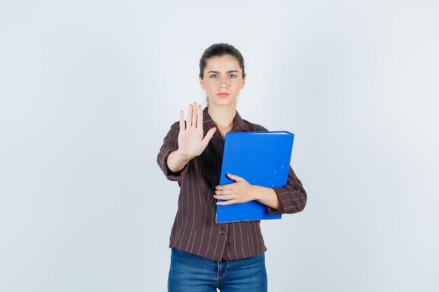 Jovem senhora de camiseta, jeans, mostrando o gesto de parar, segurando a pasta e olhando séria, vista frontal.