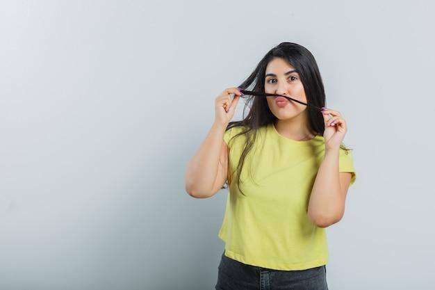 Jovem senhora de camiseta, jeans segurando a mecha como bigode e parecendo engraçada