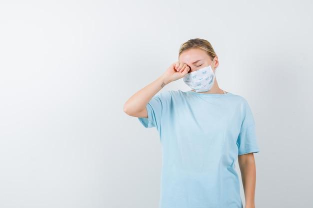 Jovem senhora de camiseta, máscara esfregando os olhos com o punho fechado e parecendo sonolenta