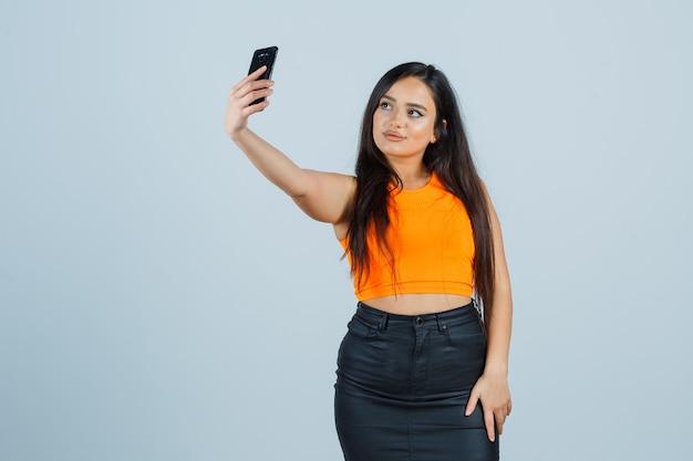 Jovem senhora de camiseta, minissaia, tirando selfie com o celular e parecendo atraente, vista frontal.