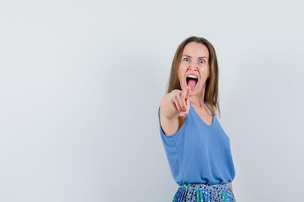 Jovem senhora de camiseta, saia apontando para a câmera e parecendo agressiva, vista frontal.