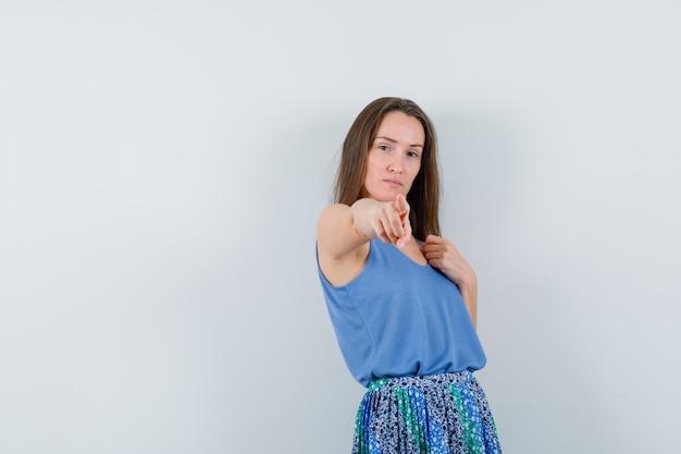 Jovem senhora de camiseta, saia apontando para a câmera e parecendo confiante, vista frontal.