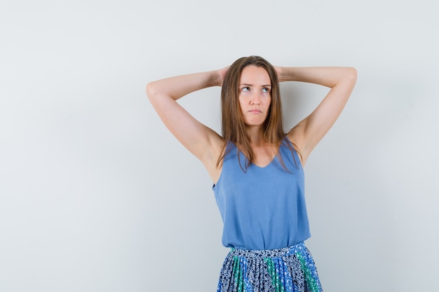 Jovem senhora de camiseta, saia de mãos dadas atrás da cabeça e parecendo hesitante, vista frontal.