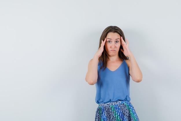 Jovem senhora de camiseta, saia esfregando as têmporas e parecendo confusa, vista frontal.