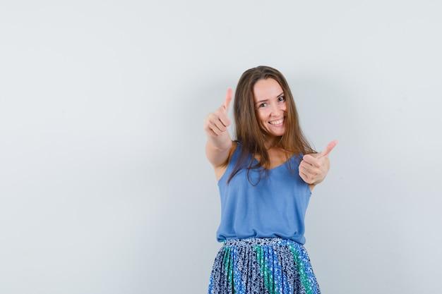 Jovem senhora de camiseta, saia mostrando dois polegares para cima e parecendo confiante, vista frontal.