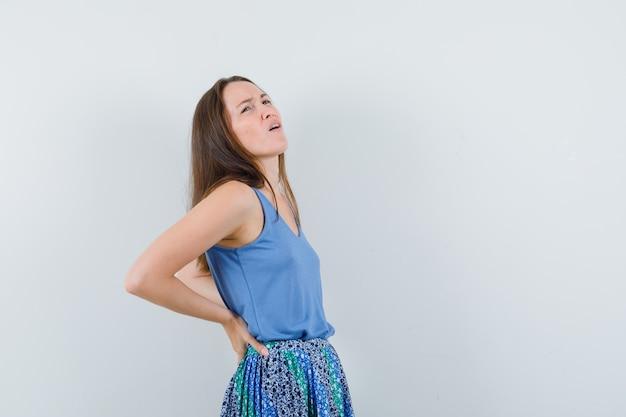Jovem senhora de camiseta, saia, sofre de dor nas costas e parece cansada, vista frontal.