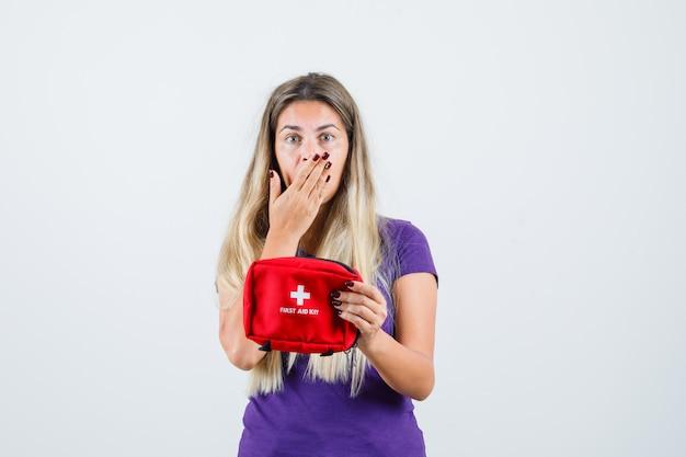 Jovem senhora de camiseta violeta, segurando o kit de primeiros socorros e olhando preocupada, vista frontal.