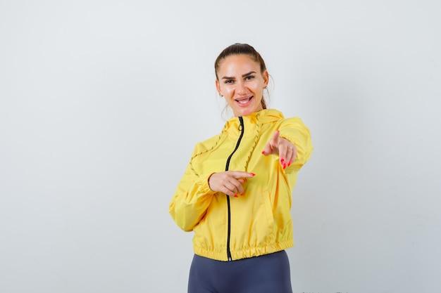 Jovem senhora de casaco amarelo, apontando e parecendo feliz, vista frontal.