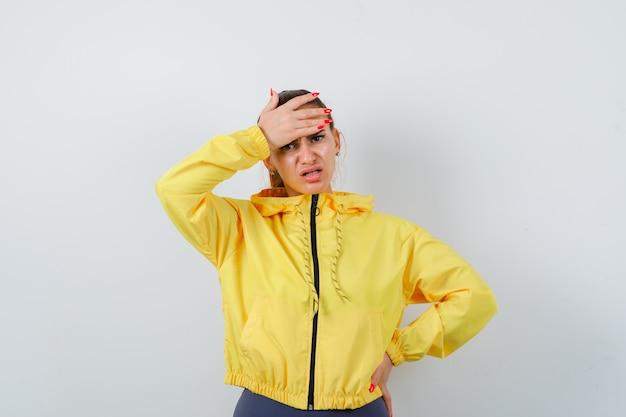 Jovem senhora de casaco amarelo com a mão na testa e olhando ansiosa, vista frontal.