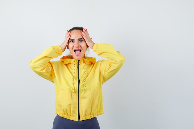 Jovem senhora de casaco amarelo com as mãos na cabeça e olhando feliz, vista frontal.