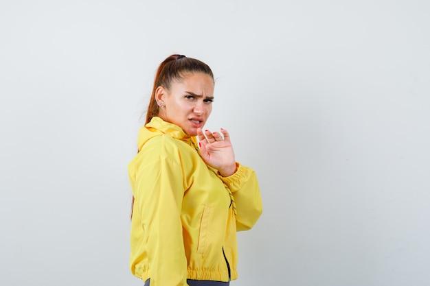 Jovem senhora de casaco amarelo, levantando a mão para se defender e parecendo ansiosa, vista frontal.