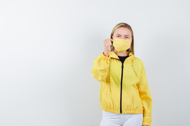 Jovem senhora de casaco, calça, máscara, ameaçando com o punho e parecendo com raiva, vista frontal.