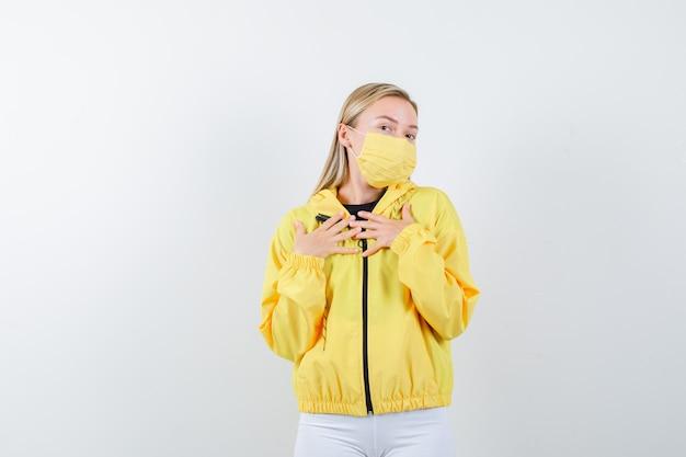 Jovem senhora de casaco, calça, máscara, mantendo as mãos no peito e parecendo agradecida, vista frontal.