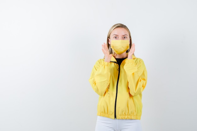 Jovem senhora de casaco, calça, máscara, mantendo as mãos perto do rosto e olhando animada, vista frontal.