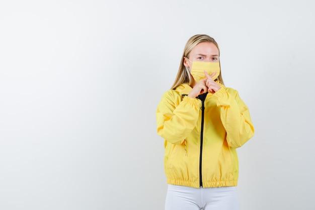 Jovem senhora de casaco, calça, máscara, mostrando o gesto de silêncio com os dedos cruzados formando um xe olhando cuidadosa, vista frontal.