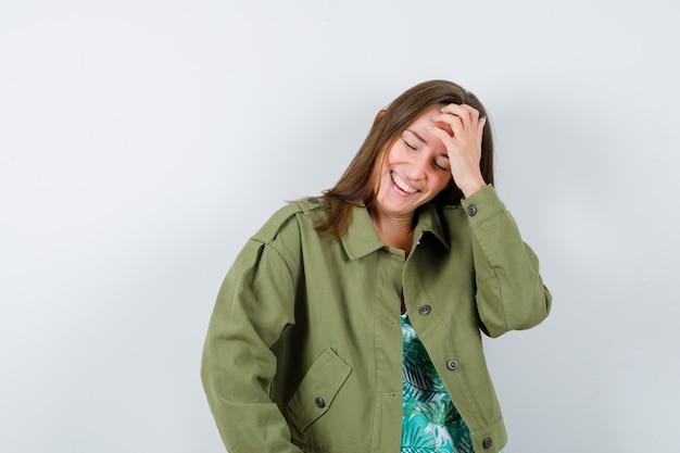 Jovem senhora de casaco verde com a mão na testa e parecendo feliz, vista frontal.