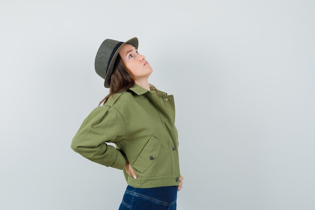 Jovem senhora de chapéu de calça jaqueta sofrendo de dor nas costas e parecendo cansada