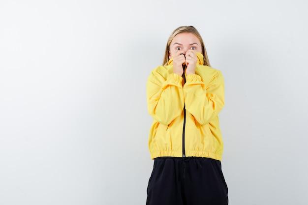 Jovem senhora de jaqueta amarela, calças puxando a gola no rosto e parecendo assustada, vista frontal.