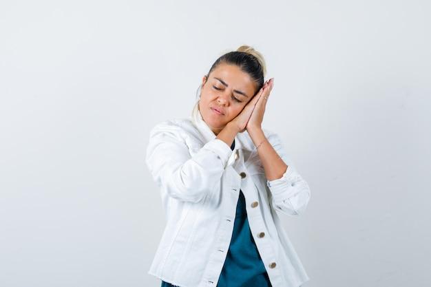 Jovem senhora de jaqueta branca apoiando-se nas palmas das mãos como travesseiro e parecendo com sono, vista frontal.