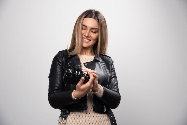 Jovem senhora de jaqueta de couro preta tirando fotos com a câmera de forma positiva e sorridente.
