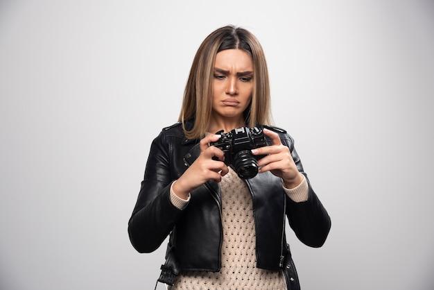 Jovem senhora de jaqueta de couro preta tirando fotos com a câmera de forma séria e profissional.