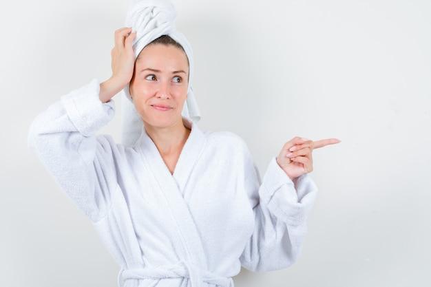 Jovem senhora de roupão branco, toalha segurando a mão na cabeça enquanto aponta para o lado direito e parece satisfeita, vista frontal.